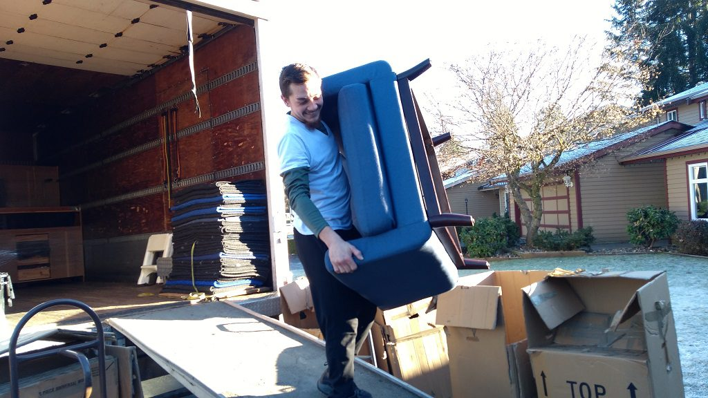 Burnaby Movers Signature Moving carrying a chair 778-325-6683